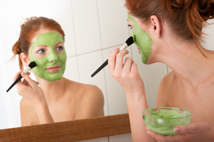 Body care series - Young woman applying facial mask